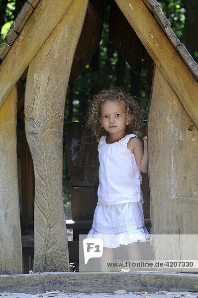 Mädchen steht im Baumhaus