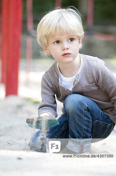 Blonder Junge spielt auf dem Spielplatz