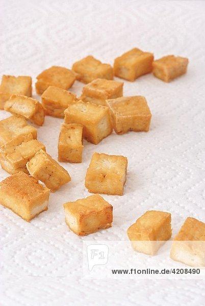 sautéed tofu laying on a white paper towel