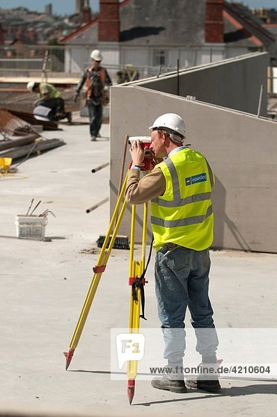 A man working on a building site surveying the location with a Leica theodolite  UK