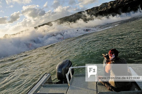 Woman on boat photographing steam rising off lava flowing into ocean  Kilauea Volcano  Hawaii Islands  United States