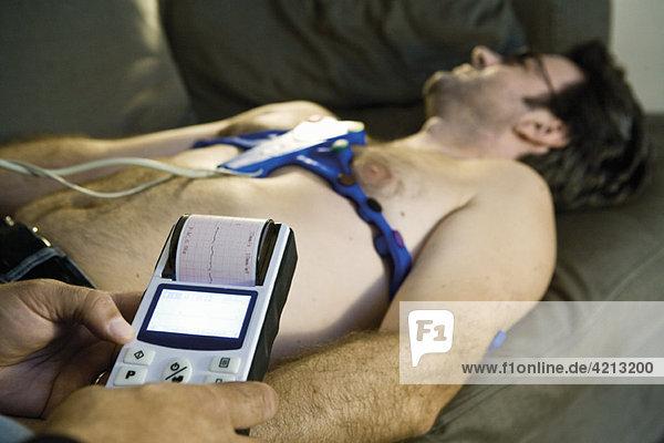 Arzt  der ein tragbares EKG (Elektrokardiogramm) am Patienten zu Hause durchführt.