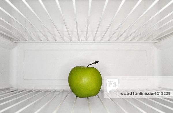 Einzelner Apfel im Kühlschrank im Regal sitzend Einzelner Apfel im Kühlschrank im Regal sitzend