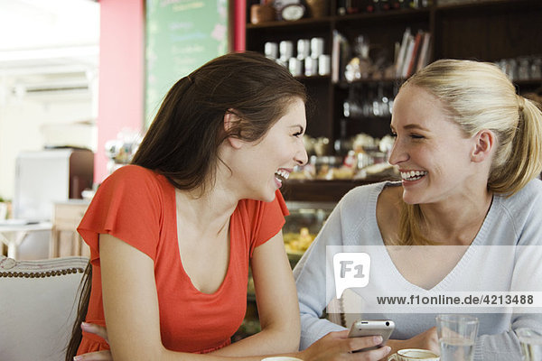 Female friends together at cafe  laughing