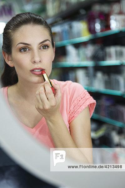 Frau probiert Lippenstift im Laden an