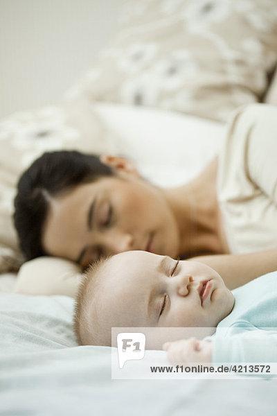 Babyschlaf auf dem Bett mit Mutter