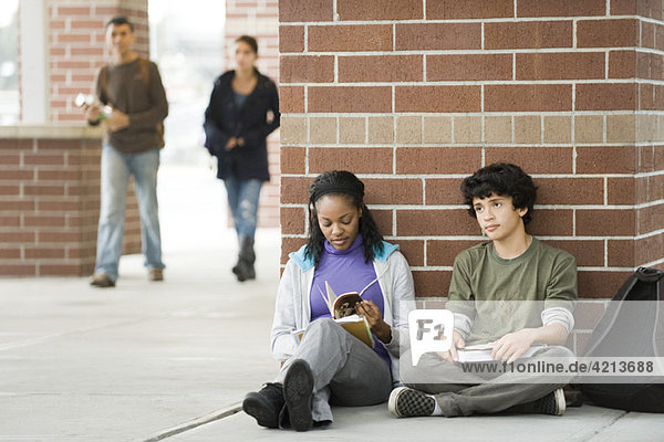 Students sitting together on sidewalk outside school