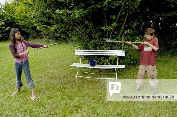 Two children fighting with bamboo water guns