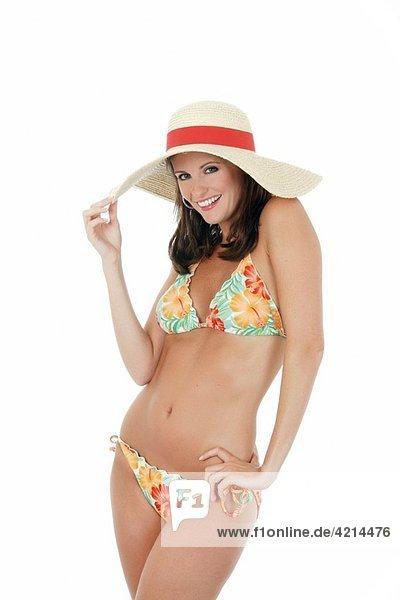 Beautiful and sexy Caucasian waman in a flowered bikini wearing a hat