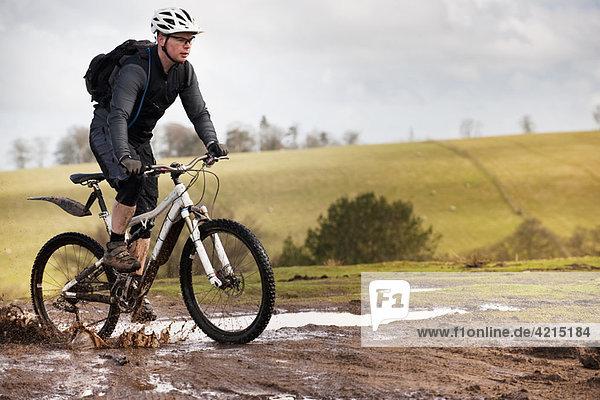 Mann auf dem Mountainbike durch den Schlamm