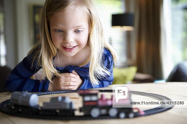 Mädchen spielen mit der Spielzeugeisenbahn