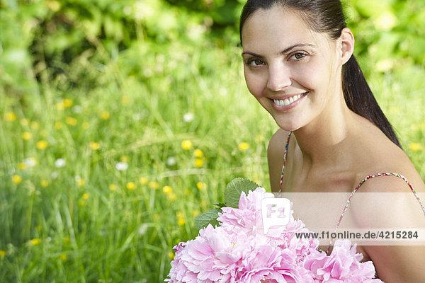 Frau mit Blumenstrauß im Garten
