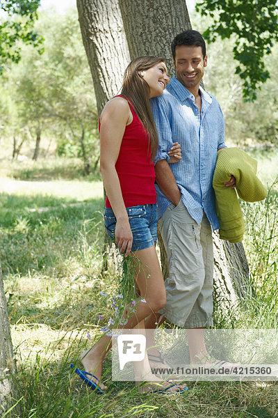 Junges Paar beim gemeinsamen Spaziergang im Wald