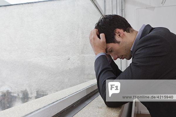 Mann  der nach einem Tag Arbeit nachdenkt.