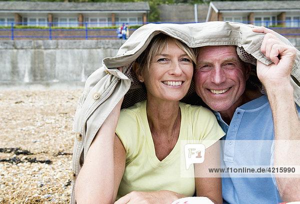 Seniorenunterkunft unter Mantel am Strand