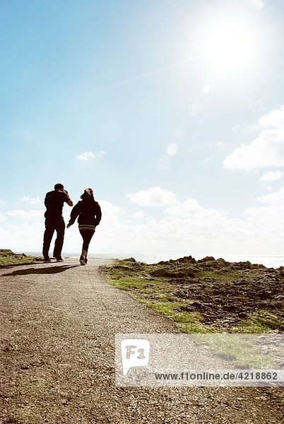 Rearview young male female couple walking along coastal path in bright sunlight