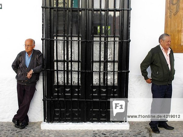 adults resting on a street in the village of Mijas on the Costa del Sol  Andalucia  Spain