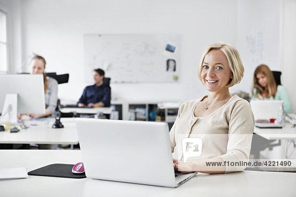 Frau sitzend am Computer bei der Arbeit