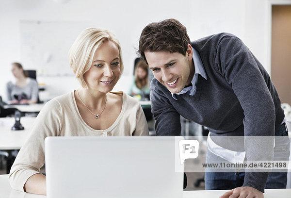 Kollegen helfen sich gegenseitig durch den Computer