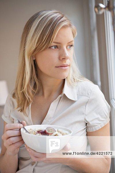 Frau beim Frühstücken am Fenster