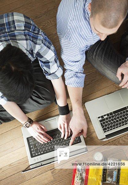 Zwei Menschen helfen sich gegenseitig am Computer.