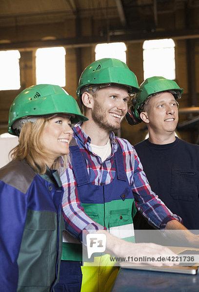 Drei Arbeiter mit grünen Helmen Drei Arbeiter mit grünen Helmen