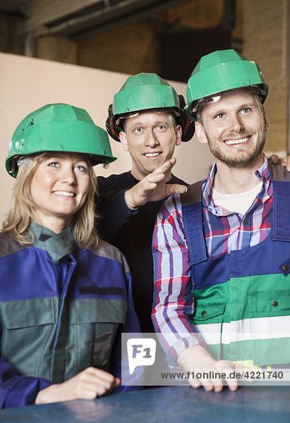 Drei woking people in grünen Helmen Drei woking people in grünen Helmen