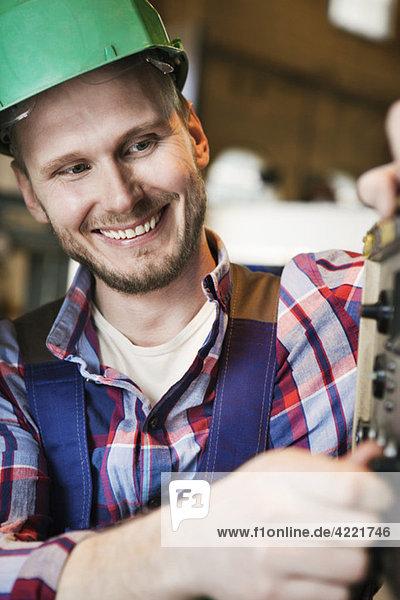 Industriearbeiter mit grünem Helm Industriearbeiter mit grünem Helm