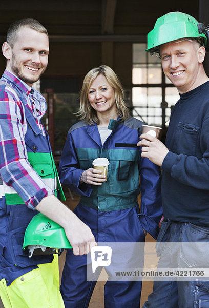 Drei Industriearbeiter machen eine Pause Drei Industriearbeiter machen eine Pause