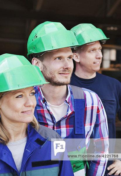 Drei Kollegen mit grünen Helmen Drei Kollegen mit grünen Helmen