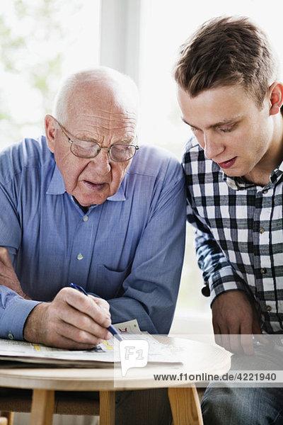 Männer lösen Kreuzworträtsel