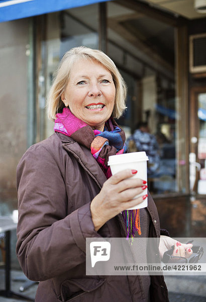 Woman with take away coffee outside