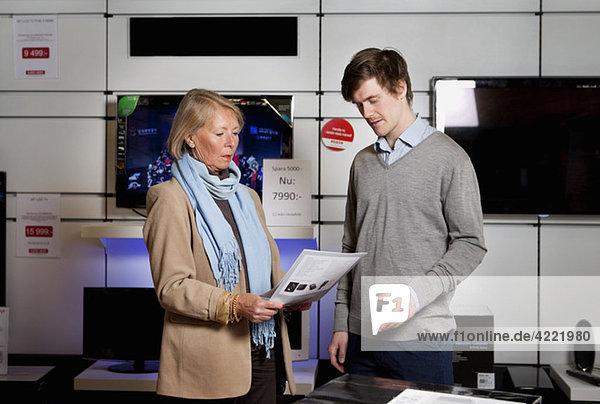 Frau fragt Verkäufer im TV-Geschäft