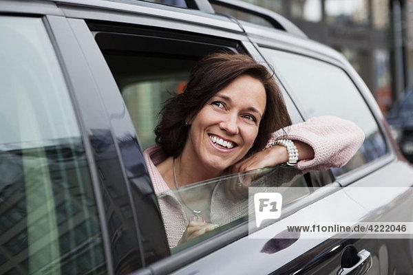 Frau  die sich aus dem Autofenster lehnt.