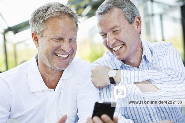Zwei Freunde mit Handy