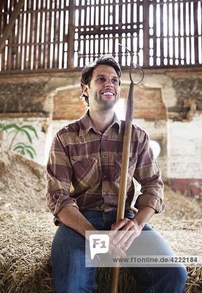 Glücklicher Bauer mit Heugabel