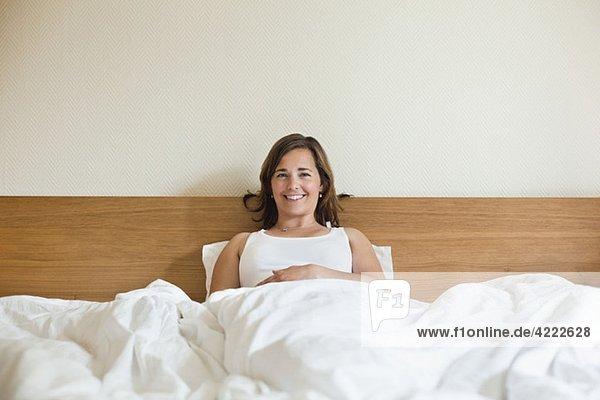 Glückliche Frau im Bett sitzend