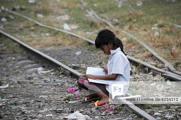 Cambodian Girl do school work on an old railway track