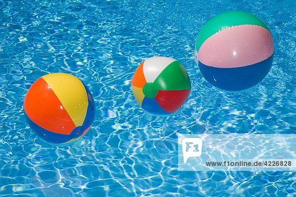 Beach balls in a sparkling blue swimming pool