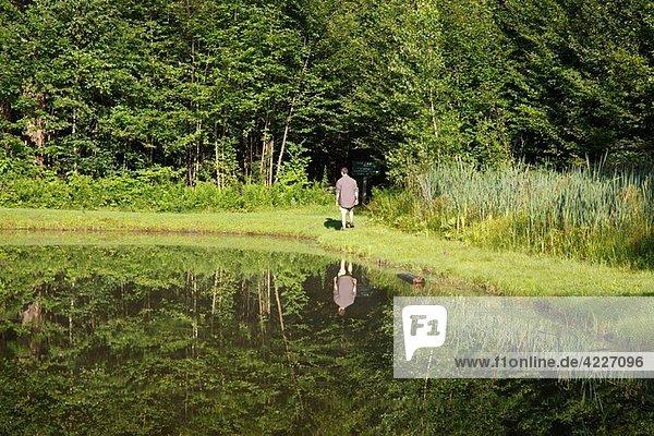 A man walks around Wildlife Pond at Bretzfelder Memorial Park in Bethlehem  New Hampshire