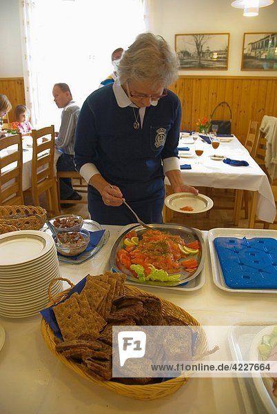 Senior woman taking raw-pickled salmon at self-service seafood buffet Reposaari district Pori Finland Europe