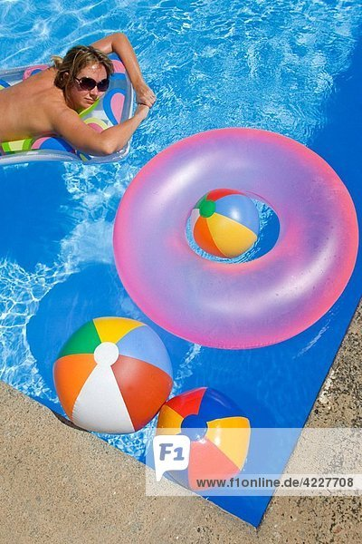 Bright blue swimming pool with beachbalsl and a woman on a lilo
