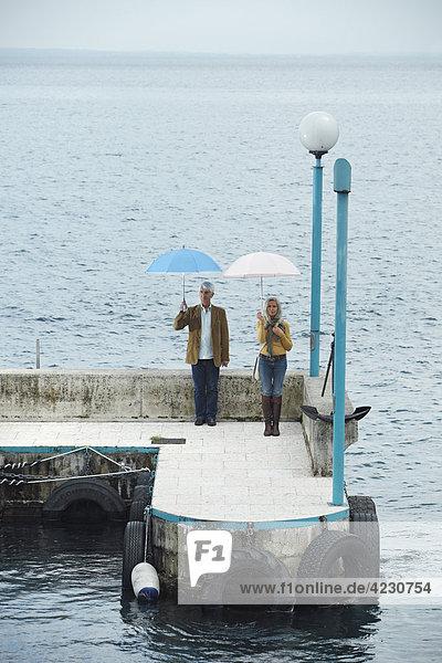 Seniorenpaar steht mit Regenschirmen auf einem Kai  Italien  Gardone Riviera