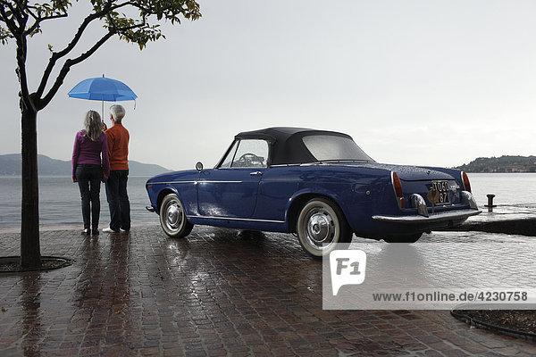 Seniorenpaar mit Oldtimer und Regenschirm am Kai  Italien  Gargnano