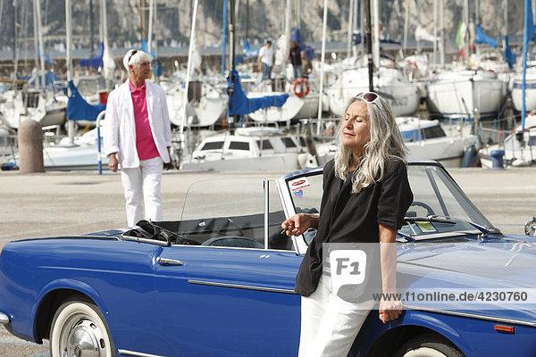 Seniorenpaar mit Cabrio am Yachthafen  Italien  Linfano