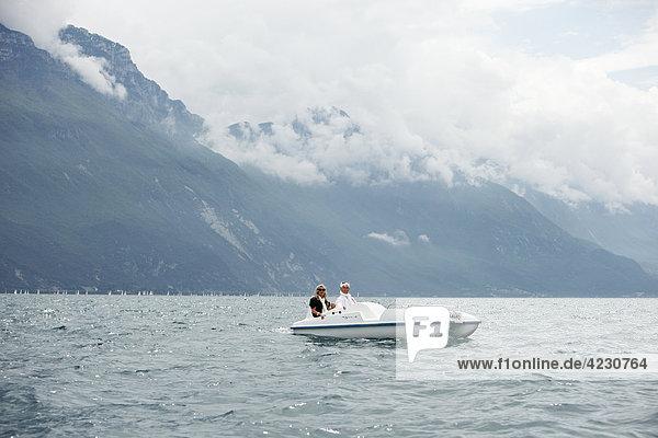 Seniorenpaar mit Tretboot vor Berglandschaft  Italien  Riva del Garda  Gardasee