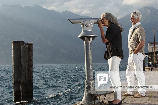 Seniorenpaar mit Münzfernrohr schaut aufs Wasser  Italien  Malcesine