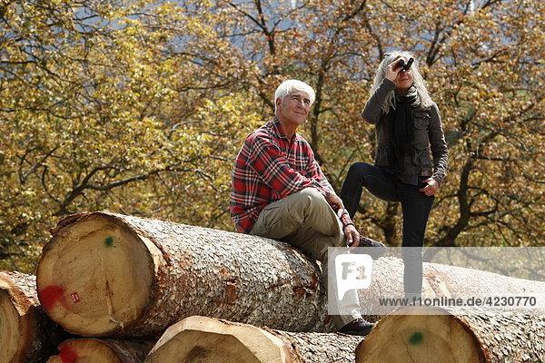 Seniorenpaar mit Fernglas auf Baumstämmen  Italien  Telve