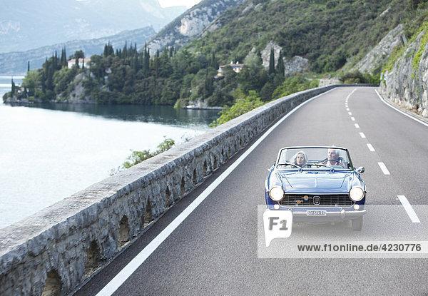 Seniorenpaar fährt mit Cabrio auf Küstenstraße  Italien  Navene