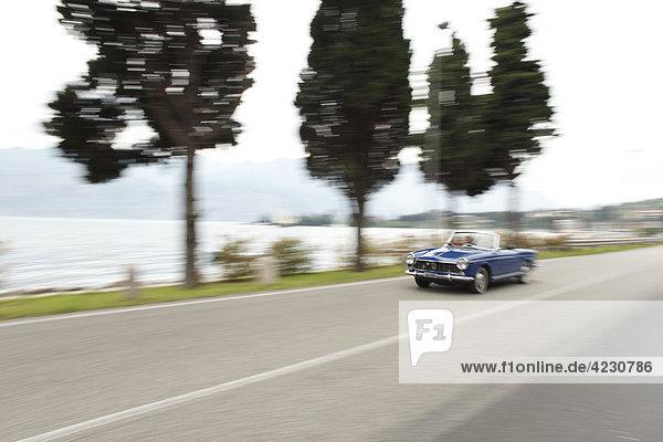Seniorenpaar fährt mit Cabrio auf Küstenstraße  Italien  Gardasee East Bay